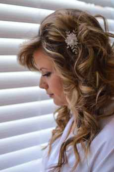 close up side view photo of woman in white top standing beside window with venetian blinds