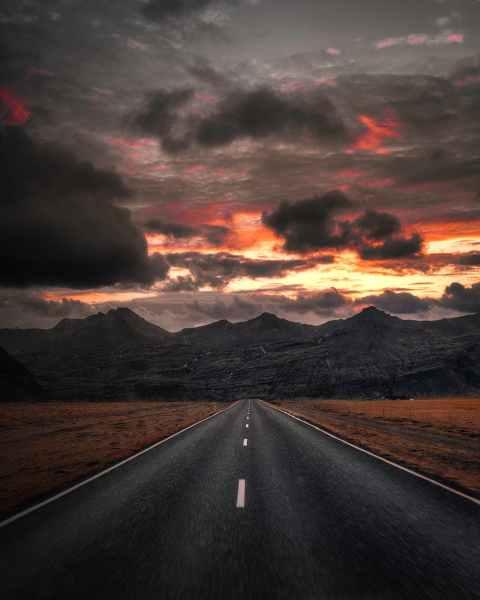 black asphalt road near mountains under cloudy sky